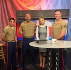"""Lacey Lett, host of Oklahoma City's Channel 4's """"Rise and Shine Morning Show,"""" poses with Recruiting Station Oklahoma City Marines after interviewing them about the USA Wrestling Girls Folkstyle Nationals tournament taking place March 23-26, 2017 at the Cox Convention Center. The interview Marines were on hand to talk about their partnership with USA Wrestling, the reasons wrestlers are great fits for the Marine Corps, and the role the Marines will play at the event."""