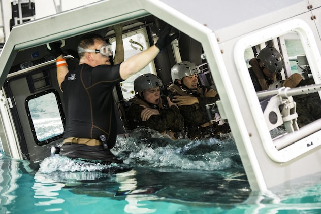 Marines with Special Purpose Marine Air-Ground Task Force - Southern Command assume brace positions as the Modular Amphibious Egress Trainer begins to submerge during Underwater Egress Training at the Water Survival Training Facility aboard Marine Corps Base Camp Lejeune, North Carolina, March 8, 2017. The purpose of the training is to teach Marines lifesaving skills in the event of an aircraft mishap in the water. (U.S. Marine Corps photo by Cpl. Melissa Martens/ Released)