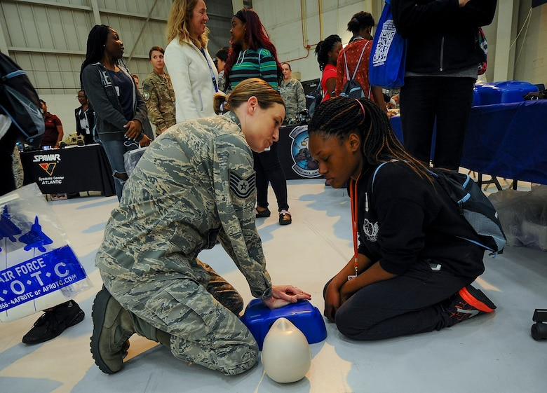 Tech Sgt. Melanie Frederick, 315th Aerospace Medicine Squadron, shows a local student how basic CPR check compressions are done at the 10th Annual Joint Base Charleston Women in Aviation Career Day March 20 at Joint Base Charleston, S.C.