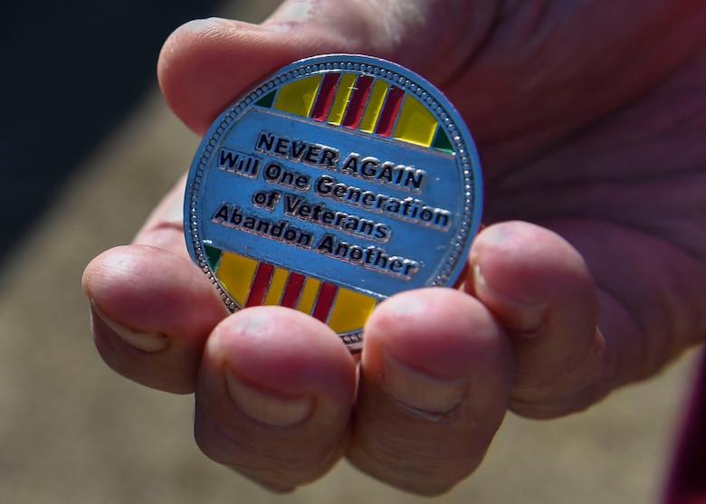 Retired U.S. Air Force Capt. William Robinson, longest surviving enlisted prisoner of war, holds a Vietnam veteran coin after an award ceremony here, March 17, 2017. Robinson was a POW for nearly eight years before being released. Now, Robinson speaks about his experience with community and military members across the country.