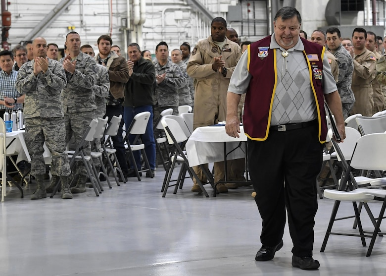 Members of the 437th Maintenance Group cheer as retired U.S. Air Force Capt. William Robinson, longest surviving enlisted prisoner of war, makes his way to the stage during an award ceremony here, March 17, 2017. Robinson was a POW for nearly eight years before being released. Now, Robinson speaks about his experience with community and military members across the country.