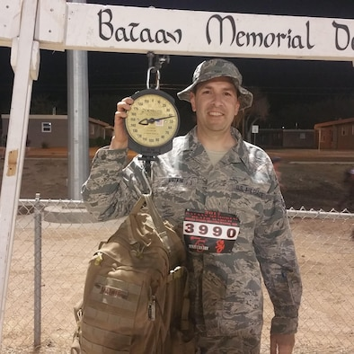 Tech. Sgt. Michael Matkin poses while weighing his pack before the Bataan Memorial Death March, White Sands Missile Range, New Mexico, March 19, 2017. The Bataan Memorial Death March commemorates the infamous 65-mile forced march of more than 60,000 American and Filipino troops during World War II. (Courtesy Photo)