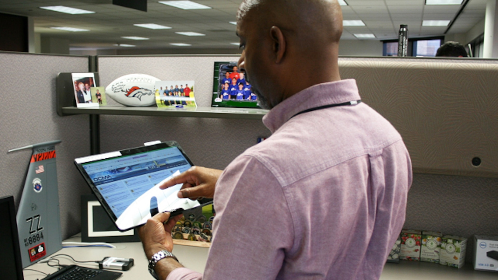 Mychael Bland, Defense Contract Management Agency Phoenix quality assurance specialist, uses a newly deployed 2-in-1 tablet computer to launch the agency's eTools applications. (Photo courtesy of DCMA Phoenix)