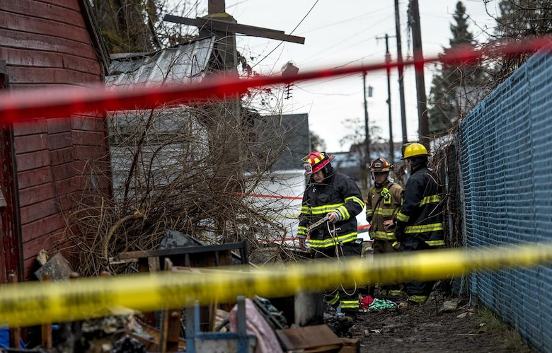 Firefighters sift through debris at a home in Medical Lake after a woman was found dead in the one-story structure that burned early Tuesday, March 14, 2017. Firefighters were called to the home near 703 E. Barker at 12:45 a.m., said Spokane County Sheriffs Deputy Mark Gregory. When they arrived on scene, firefighters saw large amounts of fire and smoke coming from the home. They were hampered by a large amount of clutter inside and out, Gregory said. While fighting the fire, they learned that a woman might still be inside, Gregory said. But firefighters were unable to enter the structure. Fire Departments from Medical Lake, Airway Heights, Spokane, Fairchild Air Force Base and Spokane County fire districts 3, 9 and 10 arrived at the scene. (Kathy Plonka / The Spokesman-Review)