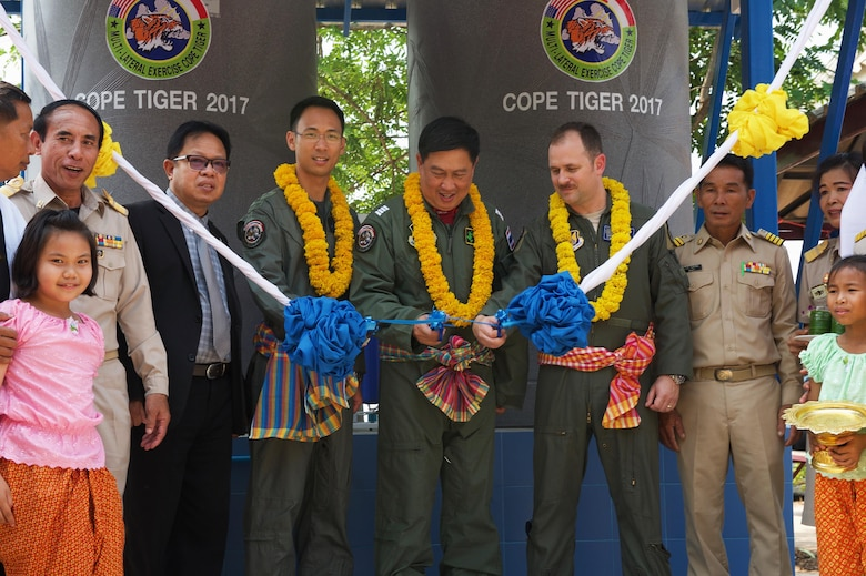 Exercise directors from the Republic of Singapore air force, Royal Thai air force and U.S. Air Force participate in a ribbon cutting ceremony to celebrate a new water filtration system donated by the three nations during the Exercise Cope Tiger 17 (CT17) combined civic action engagement at Ban Tanod Poonpol Witthaya School, Nakhon Ratchasima Province, Thailand, March 22, 2017. The combined civic action engagement provides an outlet for the countries participating in CT17 to give back to the community surrounding Korat Royal Thai Air Force Base. Over 1,200 U.S., Thai and Singaporean military members will participate in this year's annual multilateral exercise which is aimed at improving combined combat readiness and interoperability between the Republic of Singapore air force, Royal Thai air force, and U.S. Air Force, while concurrently enhancing the three nations' military relations. (U.S. Air Force photo by Staff Sgt. Kamaile Chan)