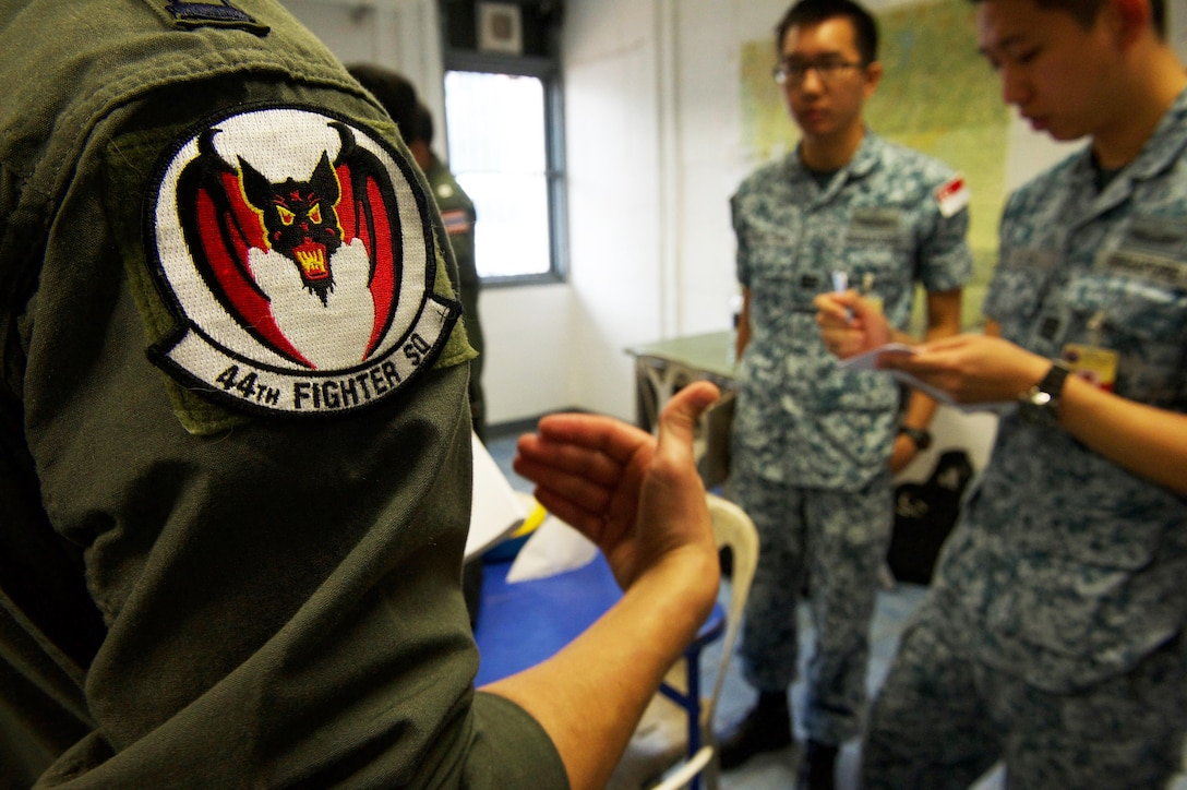A U.S. Air Force pilot with the 44th Fighter Squadron from Kadena Air Base, Japan, and members of the Republic of Singapore air force discuss mission planning during exercise Cope Tiger 2017 at Korat Royal Thai Air Force Base, Thailand, March 21, 2017. Over 1,200 U.S., Thai and Singaporean military members will participate in CT17. The annual multilateral exercise is aimed at improving combined combat readiness and interoperability between the Republic of Singapore air force, Royal Thai air force, and U.S. Air Force, while concurrently enhancing the three nations' military relations. (U.S. Air Force photo by Staff Sgt. Kamaile Chan)