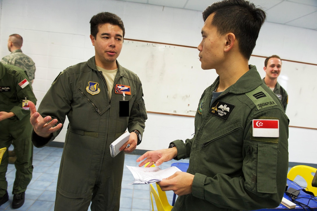 U.S. Air Force Capt. Andrew Stokes, air weapons officer with the 961st Airborne Air Control Squadron from Kadena Air Base, Japan and Republic of Singapore air force Capt. Matthew Foo discuss mission planning in preparation for a large formation exercise during exercise Cope Tiger 2017 at Korat Royal Thai Air Force Base, Thailand, March 21, 2017. Over 1,200 U.S., Thai and Singaporean military members will participate in CT17. The annual multilateral exercise is aimed at improving combined combat readiness and interoperability between the Republic of Singapore air force, Royal Thai air force, and U.S. Air Force, while concurrently enhancing the three nations' military relations. (U.S. Air Force photo by Staff Sgt. Kamaile Chan)