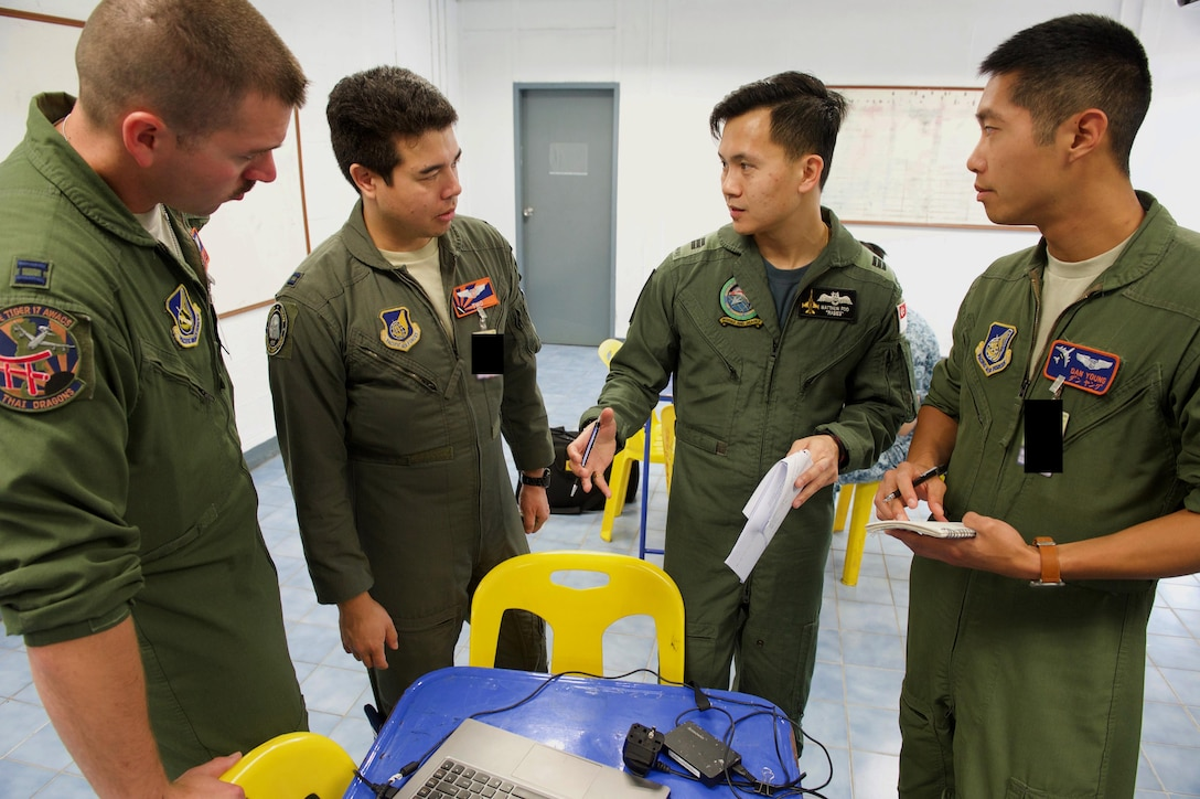 U.S. Air Force pilots with 961st Airborne Air Control Squadron from Kadena Air Base, Japan and a Republic of Singapore air force pilot discuss mission planning in preparation for a large formation exercise during exercise Cope Tiger 2017 at Korat Royal Thai Air Force Base, Thailand, March 21, 2017. Over 1,200 U.S., Thai and Singaporean military members will participate in CT17. The annual multilateral exercise is aimed at improving combined combat readiness and interoperability between the Republic of Singapore air force, Royal Thai air force, and U.S. Air Force, while concurrently enhancing the three nations' military relations. (U.S. Air Force photo by Staff Sgt. Kamaile Chan)