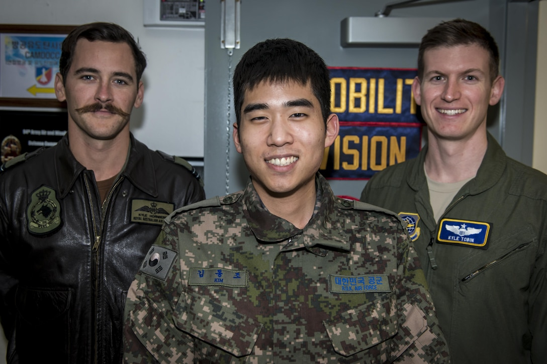 Royal Australian Air Force Flt. Lt. Kyle Hornberg, left, Republic of Korea Air Force 2nd Lt. Dongjo Kim, center, and U.S. Air Force Maj. Kyle Tobin, right, pose for a photo near their workstations in the Korean Air Operations Center at Osan Air Base, Republic of Korea, March 22, 2017. The three work together in the Air Mobility Division ensuring timely airlift support for all Key Resolve 2017 missions. Hornberg is the Air Mobility Division Multinational Coordination Center liaison officer with the Air Mobility Control Center at Royal Australian Air Force Base Richmond, Australia, Kim is an interpreting officer with the Air Component Command's join plans and coordination division at Osan AB, and Tobin is with the 621st Air Mobility Squadron at Joint Base McGuire-Dix-Lakehurst, New Jersey. (U.S. Air Force photo by Staff Sgt. Benjamin W. Stratton)