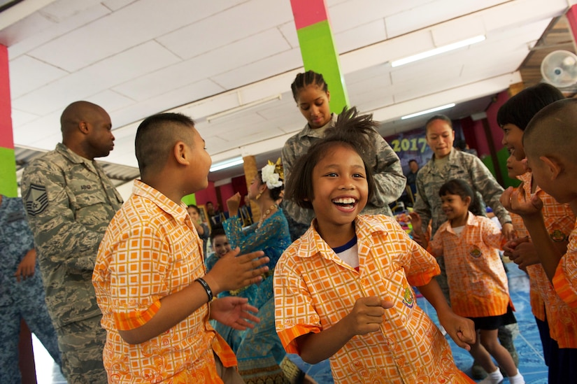 U.S. Airmen from Kadena Air Base, Japan, dance with students from Ban Tanod Poonpol Witthaya School, as the Royal Thai air force band plays music during the Exercise Cope Tiger 17 (CT17) combined civic action engagement in Thailand, March 22, 2017. The combined civic action engagement provides an outlet for the countries participating in CT17 to give back to the community surrounding Korat Royal Thai Air Force Base. Over 1,200 U.S., Thai and Singaporean military members will participate in this year's annual multilateral exercise which is aimed at improving combined combat readiness and interoperability between the Republic of Singapore air force, Royal Thai air force, and U.S. Air Force, while concurrently enhancing the three nations' military relations. (U.S. Air Force photo by Staff Sgt. Kamaile Chan)