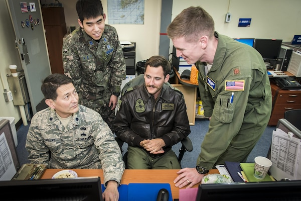 U.S. Air Force Lt. Col. Fredrick Millar, left, talks airlift strategy with Royal Australian Air Force Flt. Lt. Kyle Hornberg, right center, and U.S. Air Force Maj. Kyle Tobin, right, as Republic of Korea Air Force 2nd Lt. Dongjo Kim, left center, takes notes for sharing with ROKAF airlift counterparts in the Korean Air Operations Center's Air Mobility Division during Key Resolve 2017 at Osan Air Base, Republic of Korea, March 22, 2017. The four work together in the AMD ensuring timely airlift support, communication and execution for all Key Resolve missions. Millar is the assistant director of operations and airlift control team member with the 349th Air Mobility Operations Squadron at Travis Air Force Base, California. Hornberg is the Air Mobility Division Multinational Coordination Center liaison officer with the Air Mobility Control Center at Royal Australian Air Force Base Richmond, Australia, Tobin is with the 621st Air Mobility Squadron at Joint Base McGuire-Dix-Lakehurst, New Jersey, and Kim is an interpreting officer with the Air Component Command's join plans and coordination division at Osan AB. (U.S. Air Force photo by Staff Sgt. Benjamin W. Stratton)