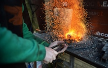 U.S. Air Force Tech. Sgt. Steven Pyott, 100th Security Forces Squadron standards and evaluations sections evaluator and blacksmith, inserts the steel into the fire Feb. 11, 2017, in Suffolk, England. The steel heats rapidly because the coals act like an oven, trapping the heat. (U.S. Air Force photo by Airman 1st Class Tenley Long)