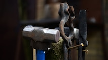 """Blacksmithing tools hang from a wooden post Feb. 11, 2017, in Suffolk, England. Blacksmithing began during the """"Iron Age"""" and over the years the tools evolved to better assist the handler. (U.S. Air Force photo by Airman 1st Class Tenley Long)"""