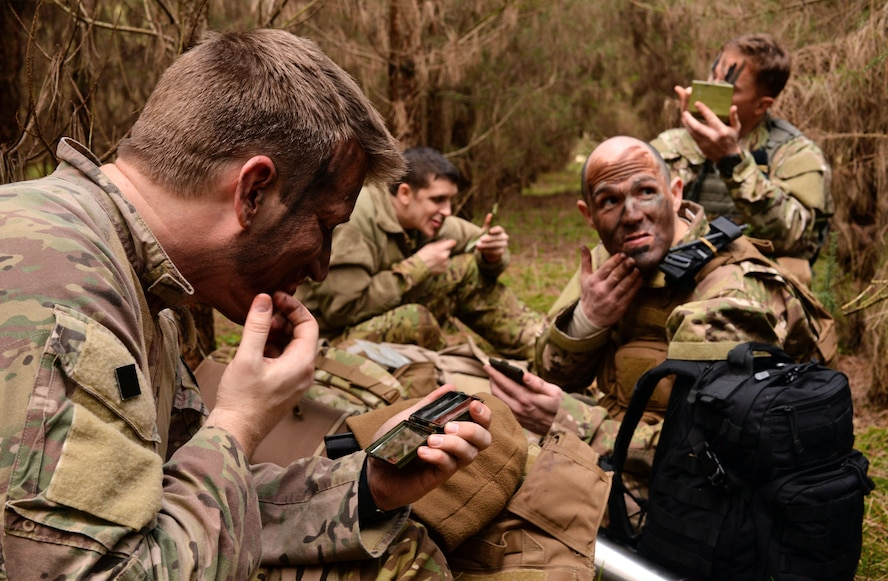 U.S. Air Force Airmen from the 352nd Special Operations Group apply camouflage paint to their faces March 8, 2017, at the Stanford Training Area, England. A Survival, Evasion, Resistance and Escape instructor trained Airmen how to properly apply face paint based on the environment. (U.S. Air Force photo by Senior Airman Christine Halan)