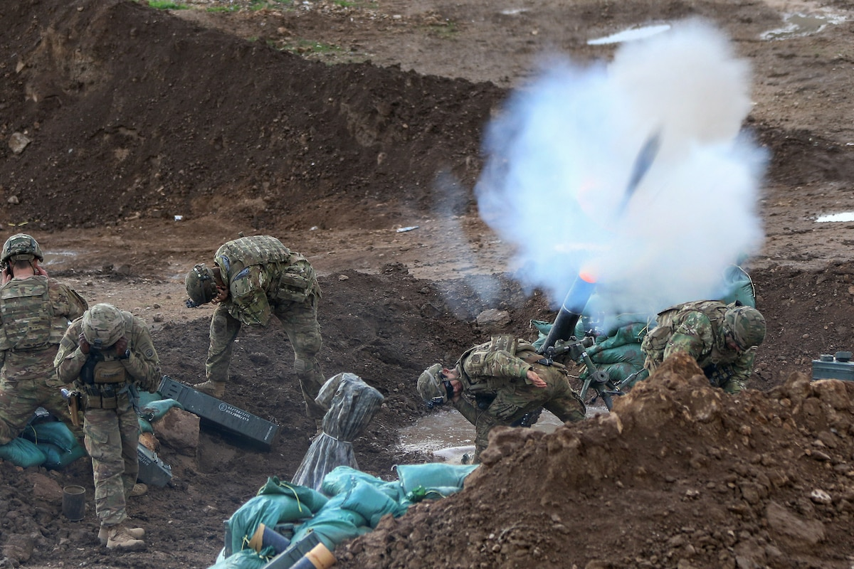 Soldiers fire mortar rounds from a trench during a fire mission in Iraq.