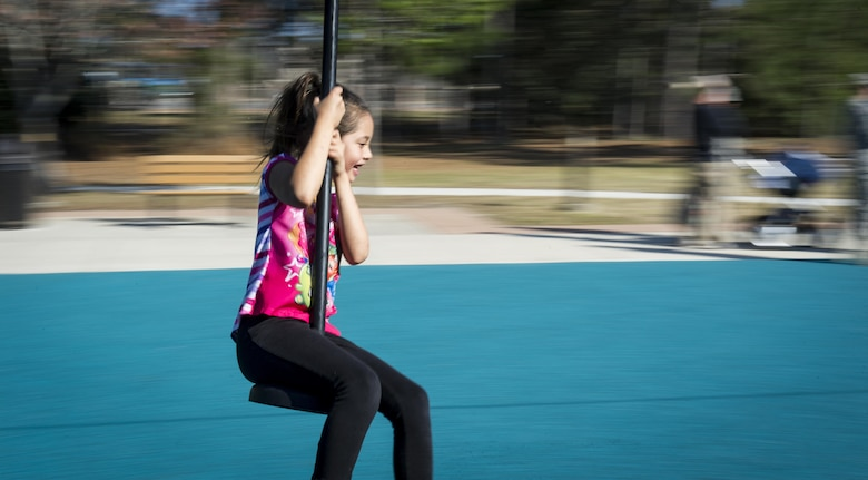 Caileign Miller, daughter of Master Sgt. Jeff Miller, a unit deployment manager with the Air Force Life Cycle Management Center, Eglin Air Force Base, Fla., rides a new zip line during the Lil' Commando Community Park reopening at Hurlburt Field, Fla., March 17, 2017. The Lil' Commando Community Park reopened after renovations which included a new zip line, playground and splash pad. (U.S. Air Force photo by Airman 1st Class Dennis Spain)