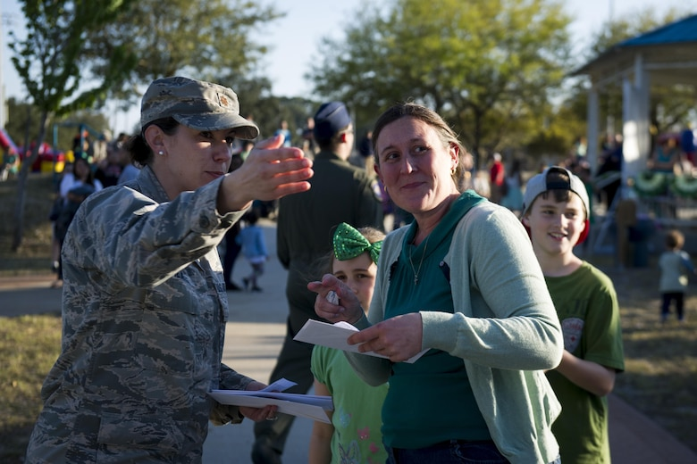 Maj. Jama Stilwell, an operations officer with the 1st Special Operations Force Support Squadron, points a raffle winner toward her prize at Hurlburt Field, Fla., March 17, 2017. The Lil' Commando Community Park reopened after renovations which included a new zip line, playground and splash pad. (U.S. Air Force photo by Airman 1st Class Dennis Spain)