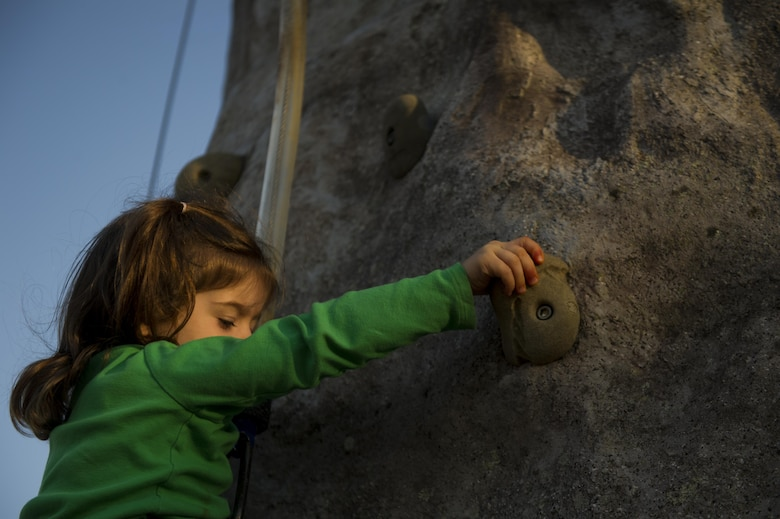 Elizabeth Waddell, daughter of Maj. John Waddell, an instructor pilot with the 19th Special Operations Squadron, climbs a rock wall at Hurlburt Field, Fla., March 17, 2017. During the Lil' Commando Community Park reopening celebration, attendees participated in festivities such as rock climbing, Segway rides and a bounce house. (U.S. Air Force photo by Airman 1st Class Dennis Spain)