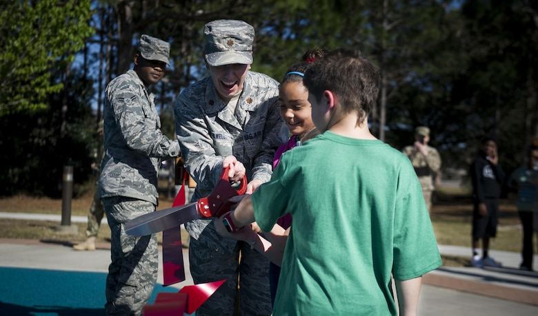 Maj. Jama Stilwell, an operations officer with the 1st Special Operations Force Support Squadron, cuts a ribbon with children during an event at Hurlburt Field, Fla., March 17, 2017. The 1st SOFSS held an event celebrating the reopening of the Lil' Commando Community Park after renovations were made including a new zip line, playground and splash pad for Air Commandos and families to enjoy. (U.S. Air Force photo by Airman 1st Class Dennis Spain)