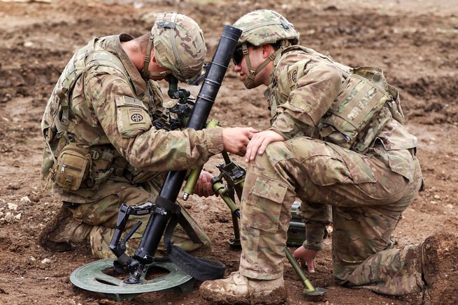 Army Spc. Jessie Patchell, left, and Pfc. Zachary Folsom set up an M224 mortar system.