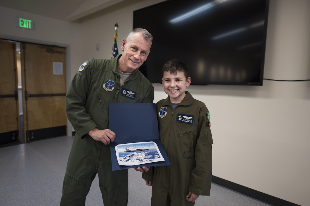 """Col. Daniel Swain, 141st Air Refueling Wing commander, presents """"Pilot for a Day"""" candidate Gabe Tesch with his pilot completion certificate March 1, 2017, at Fairchild Air Force Base, Wash. Gabe spent the day visiting several workcenters throughout the base receiving hands on instruction and briefings on what it takes to be a KC-135 pilot. The """"Pilot for a Day"""" program provides disadvantaged or seriously ill children a chance to spend the day with members of the Washington Air National Guard training as an honorary pilot. (U.S. Air Force photo by Master Sgt. Michael Stewart/Released)"""