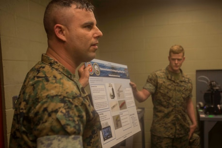 Marines hold a diagram explaining the capabilities they have with current 3-D printing technology at the additive manufacturing facility at Camp Lejeune, N.C., March 22, 2017. Nine members with the Defense Advanced Research Projects Agency visited the facility to learn more about how technology is benefitting the Marine Corps. The Marines are with 2nd Maintenance Battalion, Combat Logistics Regiment 25, 2nd Marine Logistics Group. (U.S. Marine Corps photo by Pfc. Abrey Liggins)