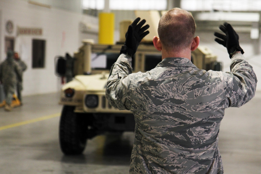 A U.S. Airmen ground guides an up-armored Humvee into position to be weighed at Joint Base McGuire-Dix-Lakehurst, N.J., during a joint inspection on March 18, 2017. The Airmen, who are assigned to the 621st Contingency Response Wing, spent the day with U.S. Army Reserve Soldiers from the 200th Military Police Command to inspect their up-armored Humvees in preparation for an air-land mission into Lakehurst Maxfield Field to kick off the ground operations of Warrior Exercise 78-17-01, which will be held March 8 to April 1, 2017. Roughly 60 units from the Army Reserve, Army, Air Force, Marine Reserves, and Canadian Armed Forces participated in the training exercise, which is a large-scale collective training event designed to assess units' combat capabilities as America's Army Reserve continues to build the most capable, combat-ready and lethal Federal Reserve force in the history of the Nation. (Army Reserve Photo by Master Sgt. Mark Bell / Released)