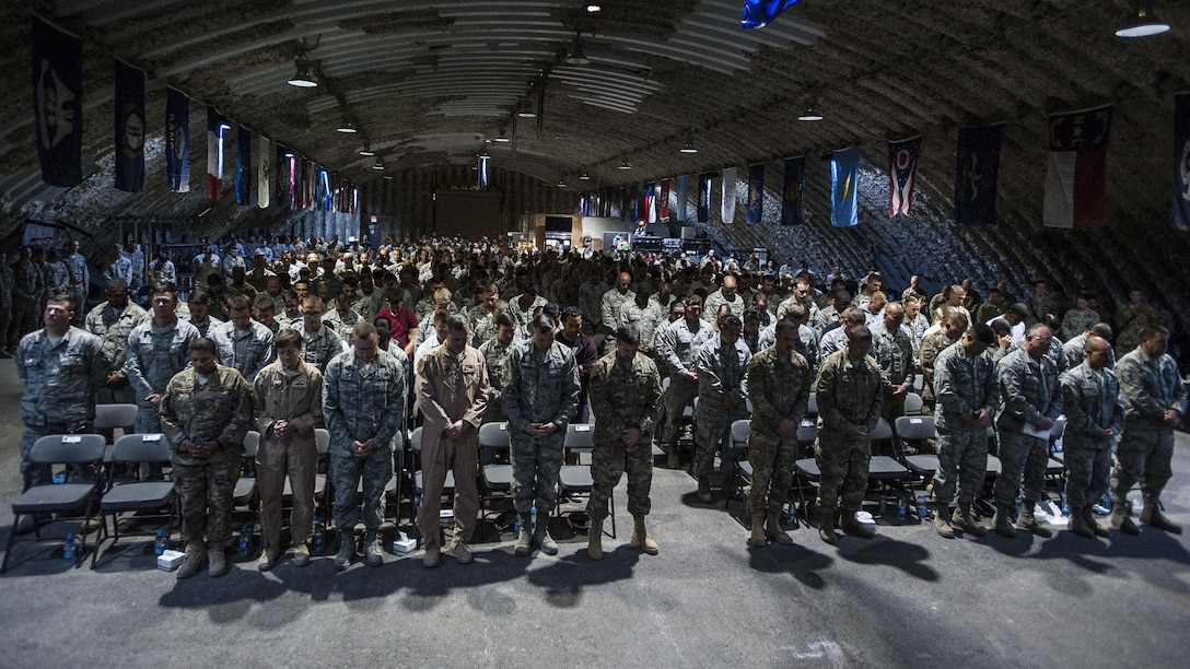 Airmen of the 332nd Air Expeditionary Wing bow their heads for an innvocation during a fallen warrior memorial ceremony Mar. 23, 2017, in Southwest Asia. The ceremony was held for Staff Sgt. Alexandria Morrow, 332nd Expeditionary Maintenance Group weapons load crew member, who died from injuries sustained while performing work duties in support of Operation Inherent Resolve. (U.S. Air Force photo by Staff Sgt. Eboni Reams)