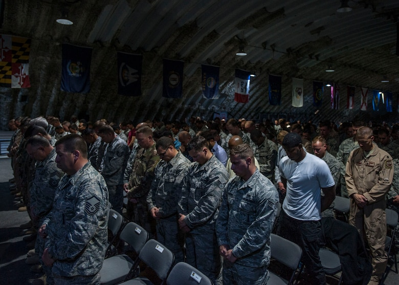 Airmen of the 332nd Air Expeditionary Wing bow their heads for an innvocation during a fallen warrior memorial ceremony Mar. 23, 2017, in Southwest Asia. The ceremony was held for Staff Sgt. Alexandria Morrow, 332nd Expeditionary Maintenance Squadron weapons load crew member, who died from injuries sustained while performing work duties in support of Operation Inherent Resolve. (U.S. Air Force photo by Staff Sgt. Eboni Reams)