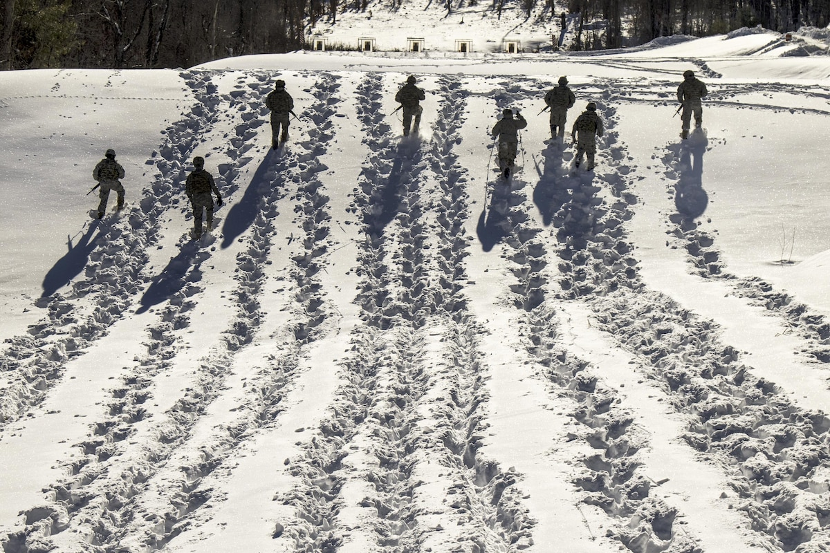 Soldiers trek through snow, leaving long trails.