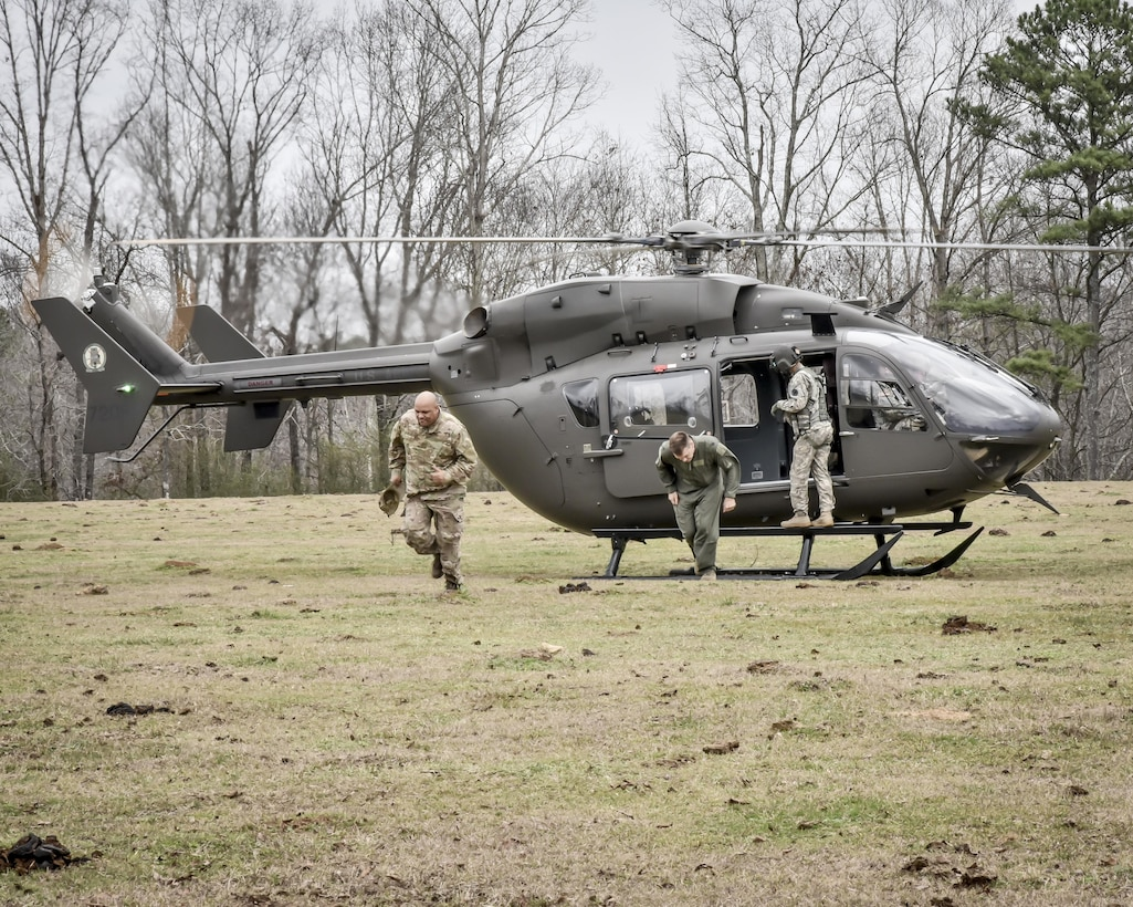 Aircrew from the 117th Air Refuelling Wing exit an Alabama Army National Guard helicopter during survival training in Hanceville, Alabama February 12, 2017. (U.S. Air National Guard photo by: Senior Master Sgt. Ken Johnson)