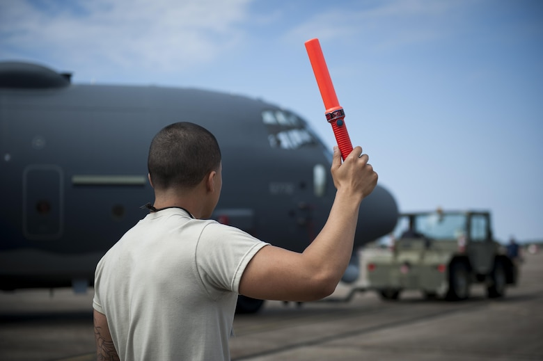 Senior Airman Adrian Gonzalez, a crew chief with the 1st Special Operations Aircraft Maintenance Squadron, wing walks an AC-130J Ghostrider gunship at Eglin Air Force Base, Fla., March 20, 2017. Gonzalez wing walked the gunship to safely escort it while it is towed into the McKinley Climatic Laboratory, a hangar used to test an aircraft's ability to operate under extreme conditions, such as low temperatures and high winds. (U.S. Air Force photo by Airman 1st Class Dennis Spain)