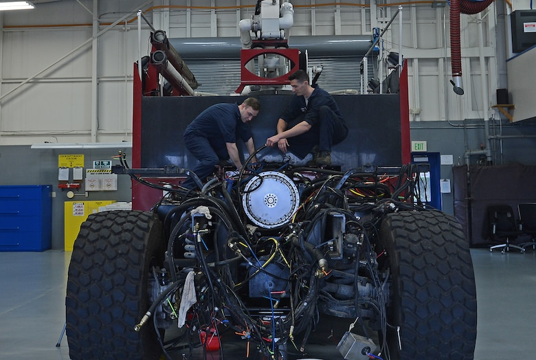 Senior Airman William Schlee (left), 627th Logistic Readiness Squadron material handling equipment mechanic and Airman 1st Class Justyn Zangwill (right), 627th LRS fire truck and refuel maintenance journeyman, detangle hoses on a McChord Field fire truck, March 21, 2017 at Joint Base Lewis-McChord, Wash. The fire truck was having mechanical issues and Schlee and Zangwill were able to identify the issue and fix it for $2,000 instead of contracting it out for an estimated cost of $70,000. (U.S. Air Force photo/Senior Airman Divine Cox)