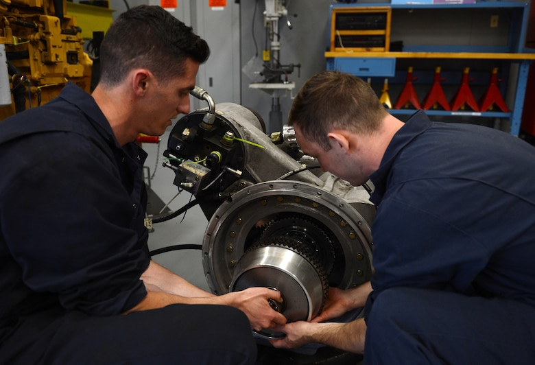 Airman 1st Class Justyn Zangwill (left), 627th Logistic Readiness Squadron fire truck and refuel maintenance journeyman and Senior Airman William Schlee (right), 627th LRS material handling equipment mechanic, install a wet clutch assembly, March 21, 2017 at Joint Base Lewis-McChord, Wash. The fire truck maintenance shop discovered an issue on a McChord fire truck and saved the Air Force thousands of dollars to repair it. (U.S. Air Force photo/Senior Airman Divine Cox)