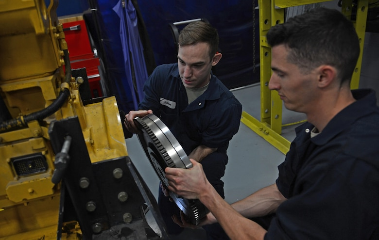 Senior Airman William Schlee (left), 627th Logistic Readiness Squadron material handling equipment mechanic and Airman 1st Class Justyn Zangwill (right), 627th LRS fire truck and refuel maintenance journeyman install a torsion coupler, March 21, 2017 at Joint Base Lewis-McChord, Wash. The torsion coupler, compresses everything together when the pumps are engaged, but the torsion reduces the shock on the springs. (U.S. Air Force photo/Senior Airman Divine Cox)