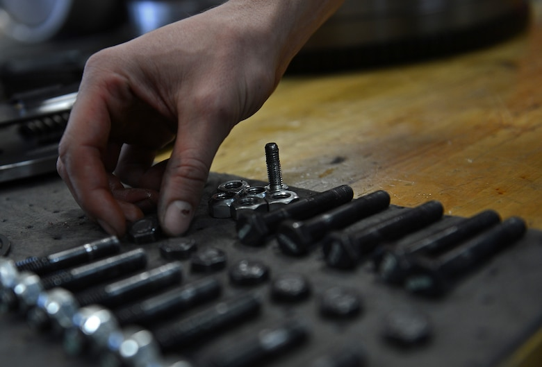 Airman 1st Class Justyn Zangwill, 627th Logistic Readiness Squadron fire truck and refuel maintenance journeyman, inspect broken bolts from a torsion coupler, March 21, 2017 at Joint Base Lewis-McChord, Wash. Zangwill had to remove the engine and the power divider assembly, to locate seven broken bolts and a broken spring inside the torsion coupler. (U.S. Air Force photo/Senior Airman Divine Cox)