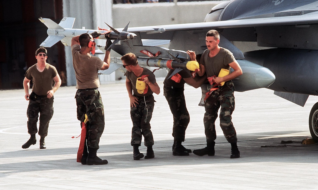 Ground crewmen remove the safety features from a pair of AIM-9 Sidewinder missiles on a 388th Tactical Fighter Wing F-16C Fighting Falcon aircraft about to depart for Saudi Arabia to take part in Operation Desert Shield. (U.S. Air Force photo)