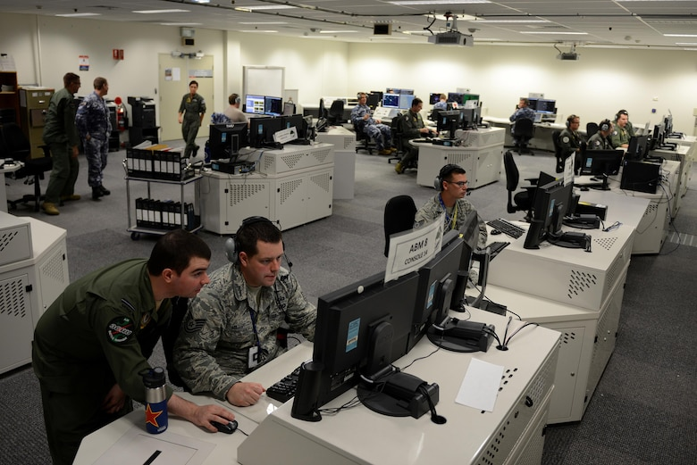 Royal Australian Air Force Flying Officer Paul Kowald, 3 Control and Reporting Unit air battle manager (bottom left), reviews exercise scenario data with U.S. Air Force Tech. Sgt. Wesley Miller, 18th Aggressor Squadron baron controller, in the Tactical Control Center, on RAAF Base Williamtown, New South Wales, Australia, March 23, 2017. Baron controllers are subject matter experts responsible for teaching joint and allied forces how to combat fighter tactics and capabilities of threat countries around the world both safely and effectively.(U.S. Air Force photo by Tech. Sgt. Steven R. Doty)
