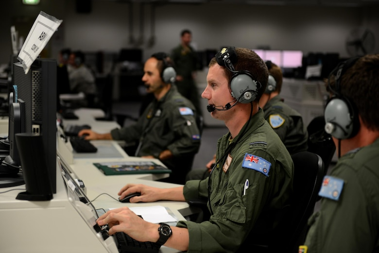 "Royal Australian Air Force Flying Officer ""Wally"", 41 Wing Surveillance and Control Training Unit air battle manager, debriefs with his counterpart in the Tactical Control Center, on RAAF Base Williamtown, New South Wales, Australia, March 23, 2017. Throughout the duration of the exercise, air battle managers are primarily responsible for command and control of the RAAF 'Blue Air' forces and for overseeing battle management operations when scenarios are active. (U.S. Air Force photo by Tech. Sgt. Steven R. Doty)"