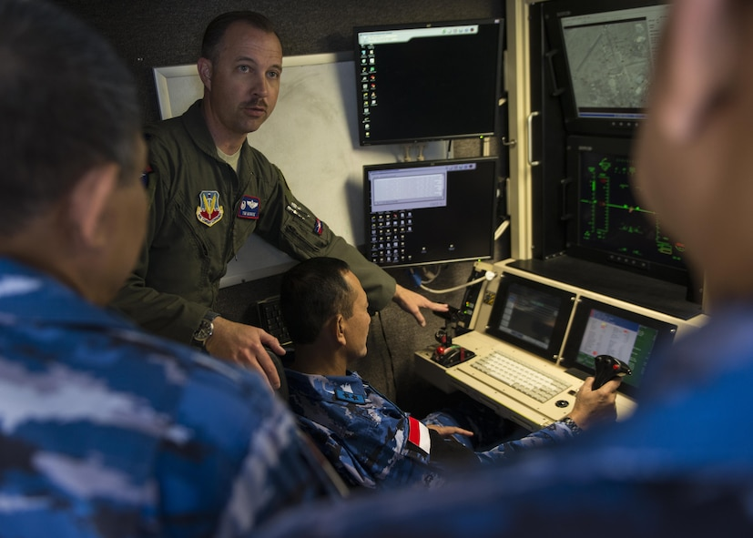 Lt. Col. Timothy Monroe, the 9th Attack Squadron commander, shows Maj. Gen. Dedy Permadi, an Indonesian Air Force officer, how to operate a remotely piloted aircraft, via a flight simulation, during a distinguished visitor tour at Holloman Air Force Base, N.M. on March 15, 2017. Members of the IDAF visited the MQ-9 Flight Training Unit and the 16th Training Squadron here to learn about RPA flight operations. (U.S. Air Force photo by Airman 1st Class Alexis P. Docherty)