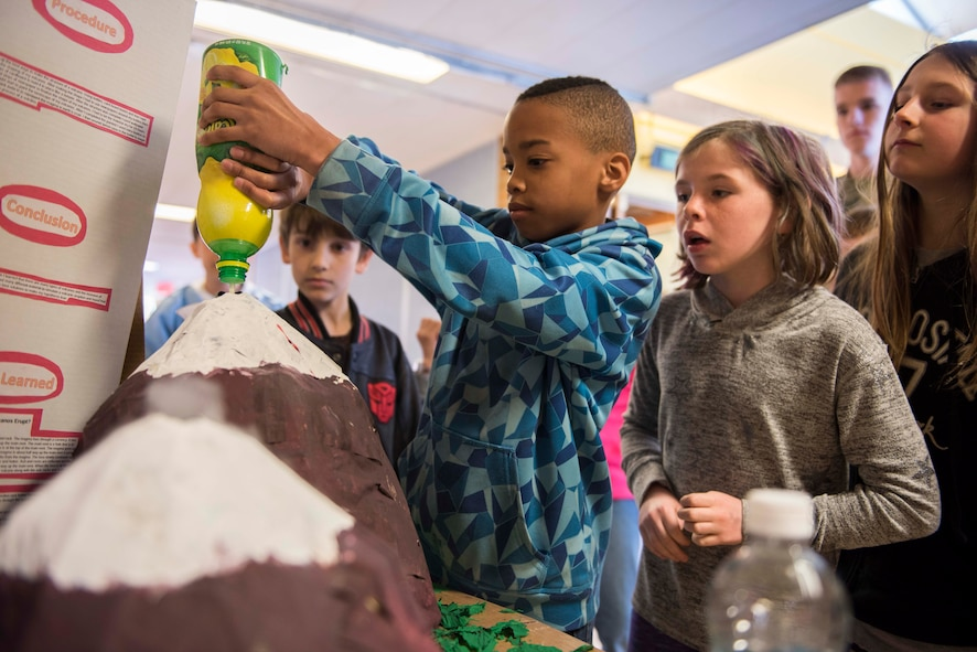 A student from Stephensen Elementary School pours lemon juice in his science fair volcano at Mountain Home Air Force Base, Idaho, March 23, 2017. The school hosts annual science fairs in order to supplement a science based curriculum for children in kindergarten through fourth grade. (U.S. Air Force photo by Senior Airman Connor J. Marth/Released)