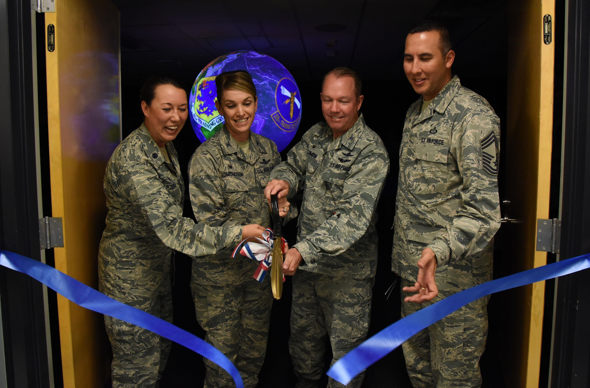 Lt. Col. Elizabeth Aptekar, 335th Training Squadron commander; Col. Michele Edmondson, 81st Training Wing commander; Col. Scott Solomon, 81st Training Group commander, and Chief Master Sgt. Randy Sabin, Air Education and Training Command weather functional manager, participate in a ribbon cutting ceremony to unveil a Science on a Sphere at the Weather Training Complex March 23, 2017, on Keesler Air Force Base, Miss. This latest training aid displays planetary data onto a suspended carbon-fiber sphere helping instructors enhance student's understanding of the atmosphere. (U.S. Air Force photo by Kemberly Groue)