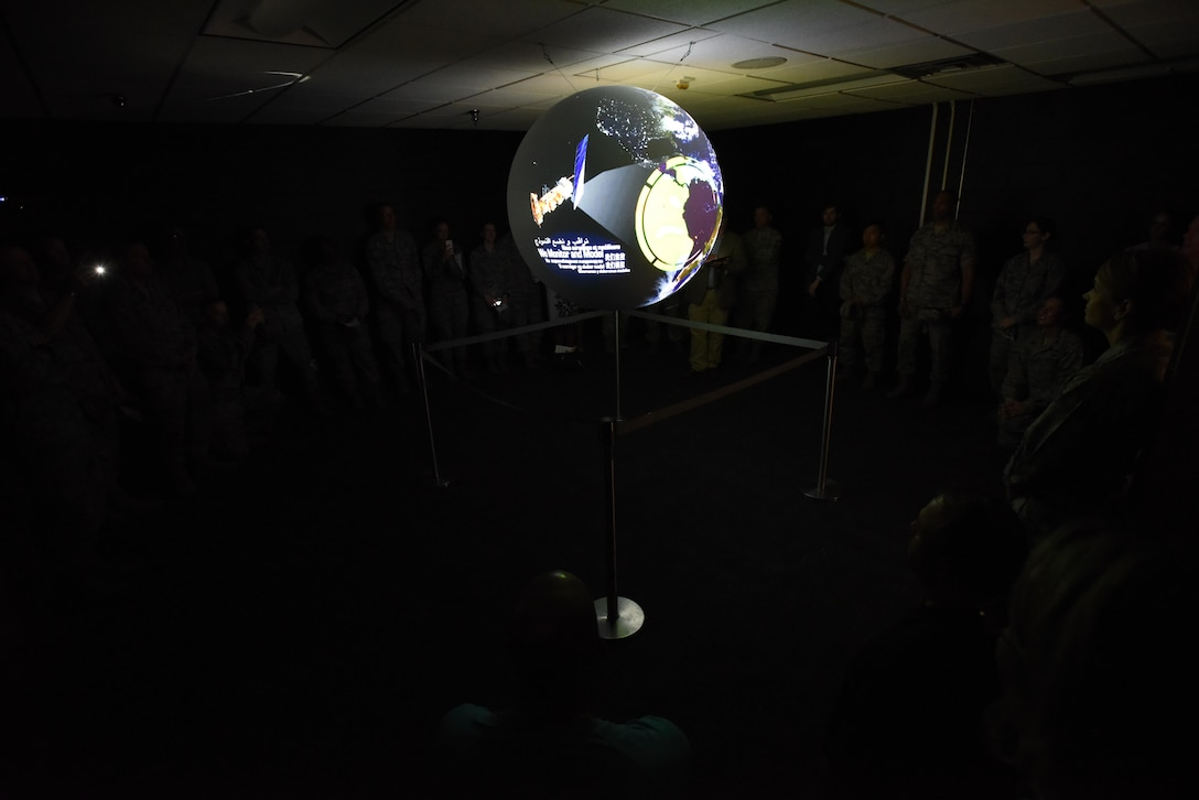 Keesler personnel receive a Science on a Sphere demonstration during a ribbon cutting ceremony at the Weather Training Complex March 23, 2017, on Keesler Air Force Base, Miss. This latest training aid displays planetary data onto a suspended carbon-fiber sphere helping instructors enhance student's understanding of the atmosphere. (U.S. Air Force photo by Kemberly Groue)