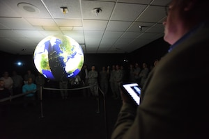 Keesler personnel watch a Science on a Sphere demonstration during a ribbon cutting ceremony at the Weather Training Complex March 23, 2017, on Keesler Air Force Base, Miss. This latest training aid displays planetary data onto a suspended carbon-fiber sphere helping instructors enhance student's understanding of the atmosphere. (U.S. Air Force photo by Kemberly Groue)