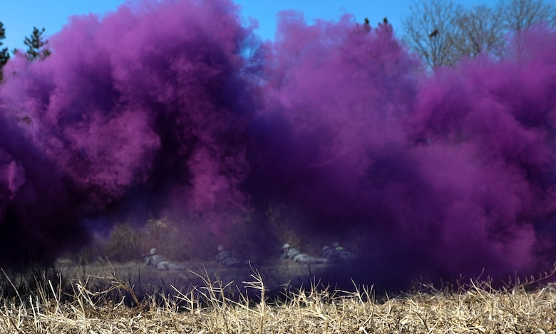 U.S. Air Force 8th Security Forces Squadron members take cover while purple smoke signals an attack during a field training exercise at Kunsan Air Base, Republic of Korea, March 17, 2017. Opposing forces attack the security forces members to test their teamwork and communication skills under stressful situations. (U.S. Air Force photo by Senior Airman Colville McFee/Released)