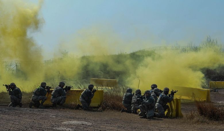 U.S. Air Force 8th Security Forces Squadron members take cover while yellow smoke signals an attack during a field training exercise at Kunsan Air Base, Republic of Korea, March 17, 2017. The training exercise is used to increase U.S. combat readiness and ultimately enhance the U.S. commitment to maintaining peace in the region. (U.S. Air Force photo by Senior Airman Colville McFee/Released)