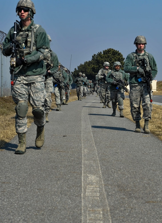 U.S. Air Force 8th Security Forces Squadron members march in a tactical staggered formation while observing their surroundings during a field training exercise at Kunsan Air Base, Republic of Korea, March 17, 2017. Tactical movements allow for military members to scan effectively and keep a safe distance between each other. (U.S. Air Force photo by Senior Airman Colville McFee/Released)