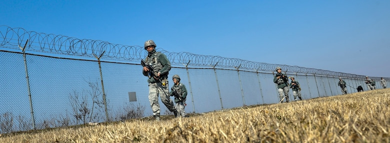 U.S. Air Force 8th Security Forces Squadron members, march in a tactical staggered formation while observing their surroundings during a field training exercise at Kunsan Air Base, Republic of Korea, March 17, 2017. U.S. Airmen work side by side to integrate air and ground operations more effectively in order to deter aggression in the region. (U.S. Air Force photo by Senior Airman Colville McFee/Released)
