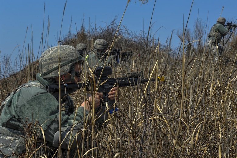 U.S. Air Force 8th Security Forces Squadron members advance through high bush while scanning for opposing forces during a field training exercise at Kunsan Air Base, Republic of Korea, March 17, 2017. Opposing forces attack the security forces members to test their teamwork and communication skills under stressful situations. (U.S. Air Force photo by Senior Airman Colville McFee/Released)
