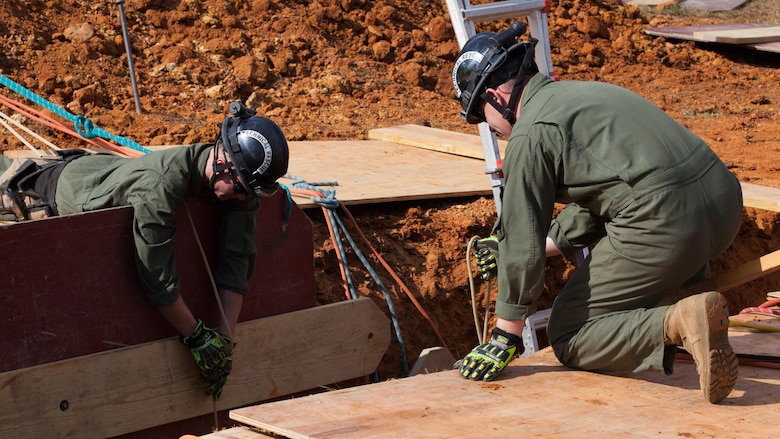 Cpl. Alexander Sutter, left, and Cpl. Vincent Leon, both Marines with Chemical Biological Incident Response Force, fix plywood into a 12-foot trench at Guardian Centers in Perry, Ga., March 20, 2017, during Exercise Scarlet Response 2017. The exercise, which goes from March 20 – 25, is the largest annual event for CBIRF, and it tests the unit's capabilities to react and respond to threats and disasters such as nuclear detonations.